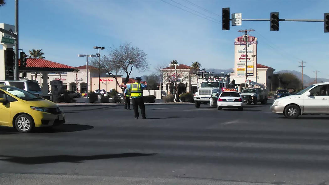 Nye County Sheriff's Auxilliary officers direct traffic by hand as crews work to upgrade the computer used to monitor the traffic signals in town. All three traffic signals on Highway 160 will r ...