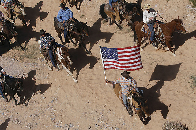 The Bundy family and its supporters fly the American flag as the family's cattle is released by the Bureau of Land Management back onto public land outside of Bunkerville on April 12, 2014. Spec ...