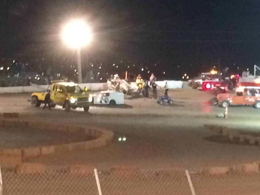 Vern Hee / Pahrump Valley Times Emergency vehicles crowd around Tony Kincaid's number 59 car after he flipped in midair and landed upside-down on turn four during one of the heat races in the St ...
