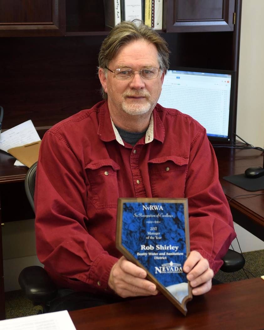 Richard Stevens/Pahrump Valley Times  Beatty Water and Sanitation District General Manager Rob Shirley at his desk with the plaque he received with the Manager of the Year award from the Nevada Ru ...