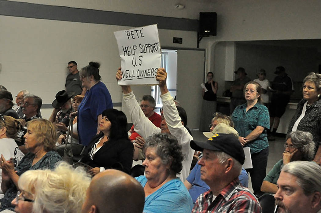 A Pahrump resident waves a sign during a 2016 meeting with state Sen. Pete Goicoechea. Goicoechea stopped in Pahrump to get input from domestic well owners ahead of Legislative Commission Subcommi ...