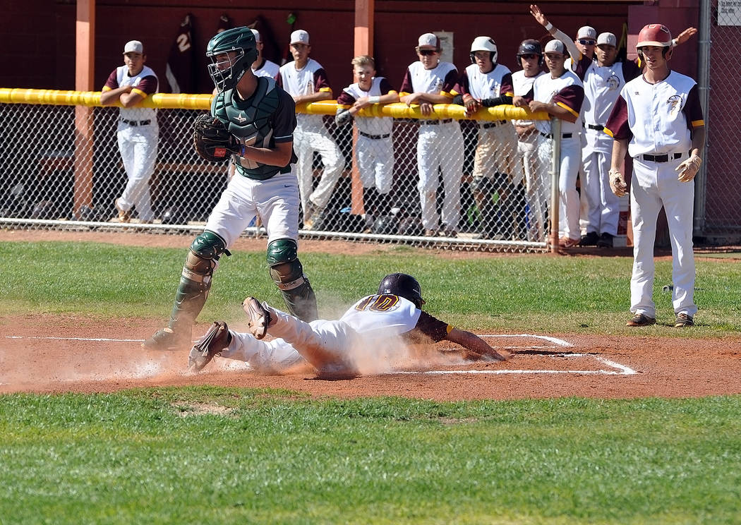 Horace Langford Jr. / Pahrump Valley Times - Drew Walker dives into home plate for the Trojans on Tuesday against Virgin Valley. The Trojans are 4-7 in non-league play, with league play starting o ...