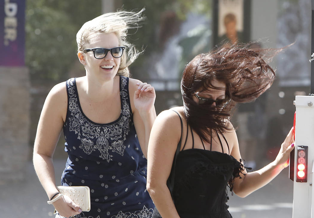 Pedestrians have their hair blown by wind as they walk along the Strip on Thursday, March 30, 2017. (Bizuayehu Tesfaye/Las Vegas Review-Journal) @bizutesfaye