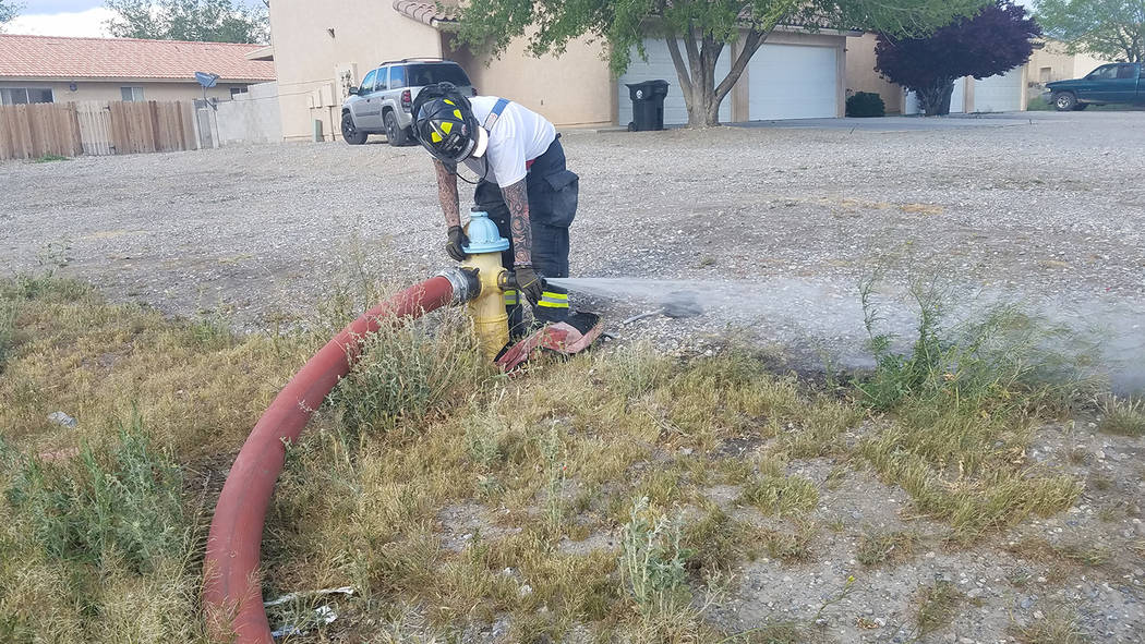 David Jacobs/Pahrump Valley Times A Pahrump Valley firefighter works on a fire hydrant along Bourbon Street. A fire burned an apartment there on March 31. No one was hurt in the fire.