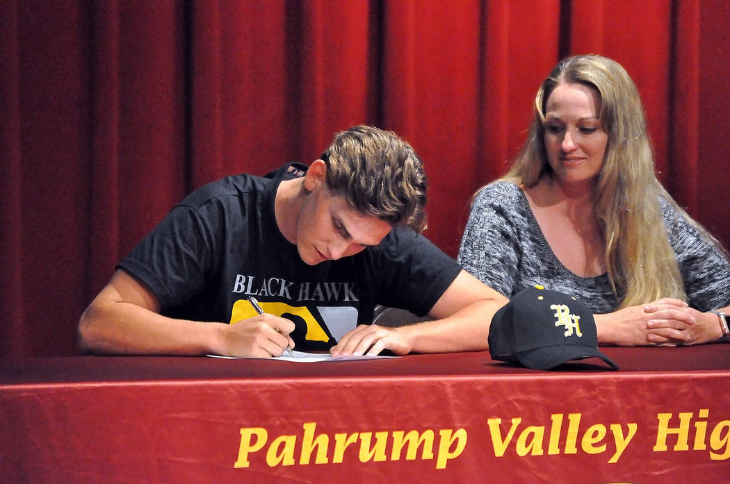 Horace Langford Jr. / Pahrump Valley Times - Parker Hart signs his college letter of intent for Black Hawk College, a small college in Moline, Illinois, while his mother, Laura Daun looks on.  Har ...