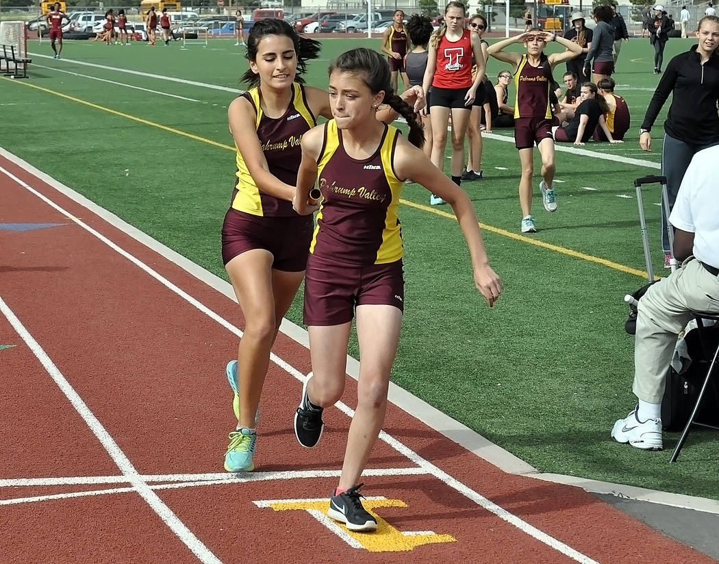 Horace Langford Jr. / Pahrump Valley Times  Senior Alicia Quiroz hands off to junior Grace Plumb in the 4x800-meter relay on April 6. The girls took first in that event and the team is composed of ...
