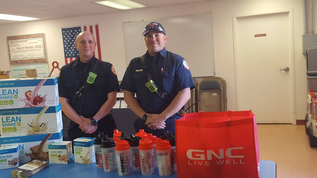Special to Pahrump Valley Times Pahrump Valley Fire and Rescue firefighters Kurt Overall, left, and James Rossen stand before cases of health food products donated by Pahrump's GNC Nutrition Cen ...