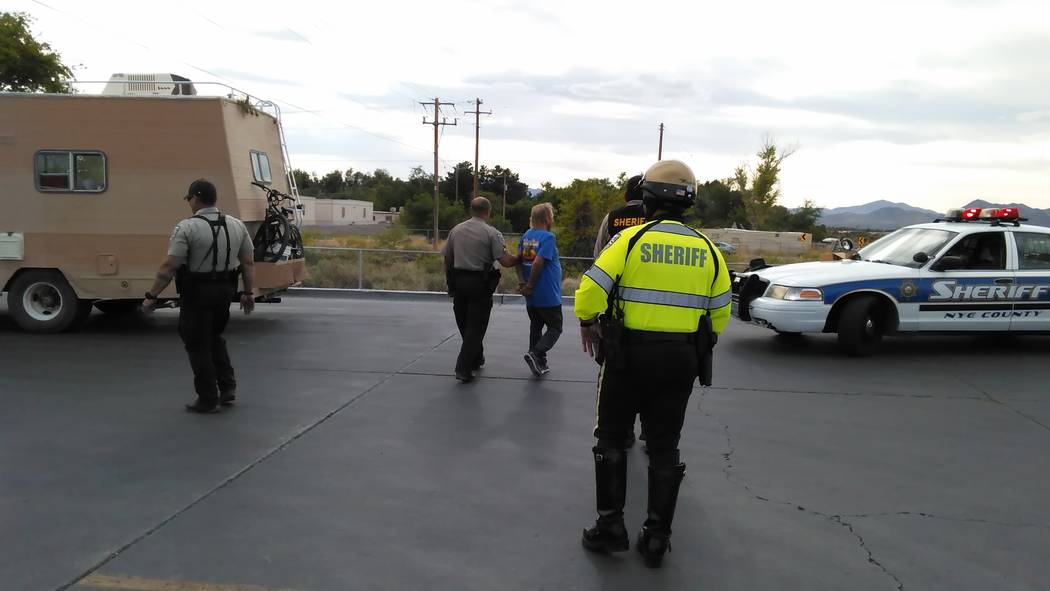 Selwyn Harris / Pahrump Valley Sheriff's deputies lead Timothy Perrson to a patrol car after he failed to pass field sobriety tests Monday afternoon, according to deputies. He was charged with D ...