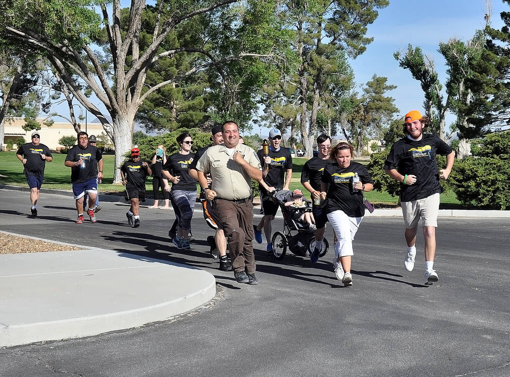 Horace Langford Jr./Pahrump Valley Times Sergeant David Boruchowitz, Nye County Sheriff's Office spokesman, runs with Ashlin Johnson and Brady Freeman at the Law Enforcement Torch Run on May 5 t ...