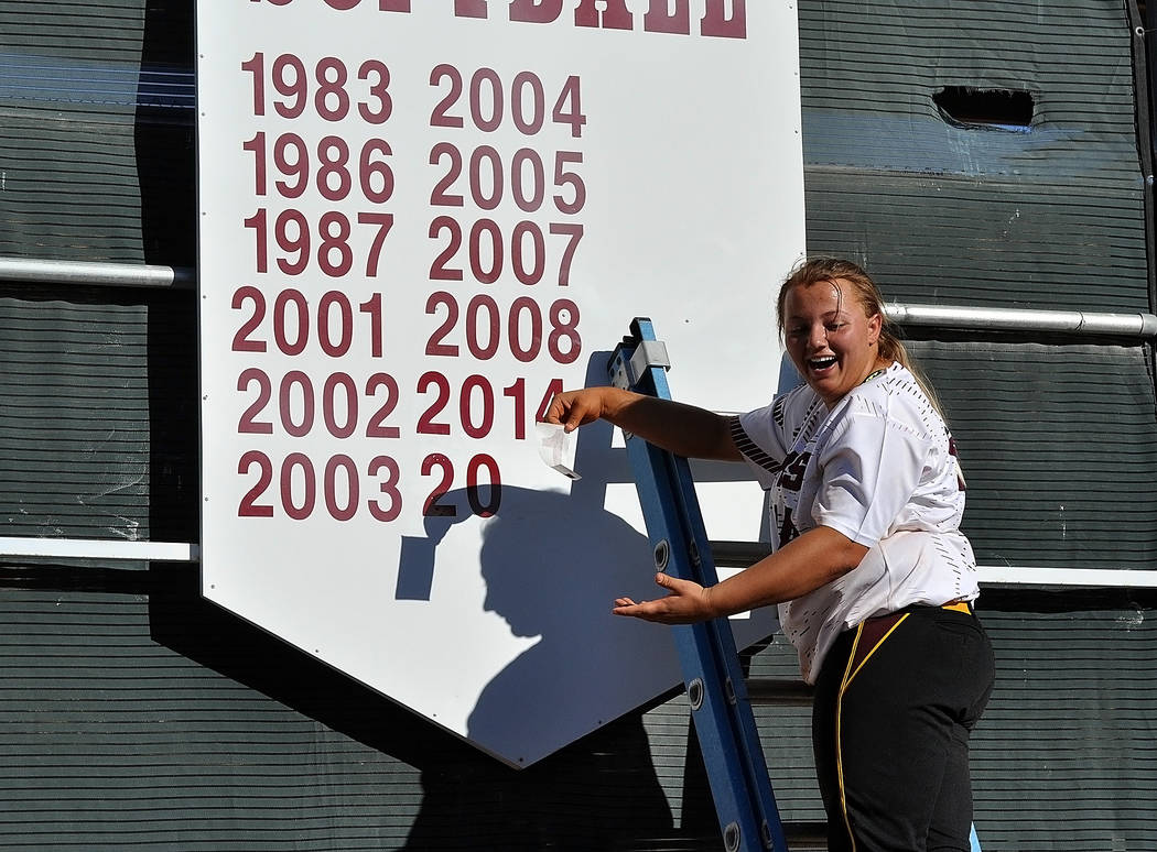 Horace Langford Jr./Pahrump Valley Times After the Mojave game on May 4, Jordan Egan adds a number to the sign on the back wall of the softball stadium. The sign lists all their league titles.