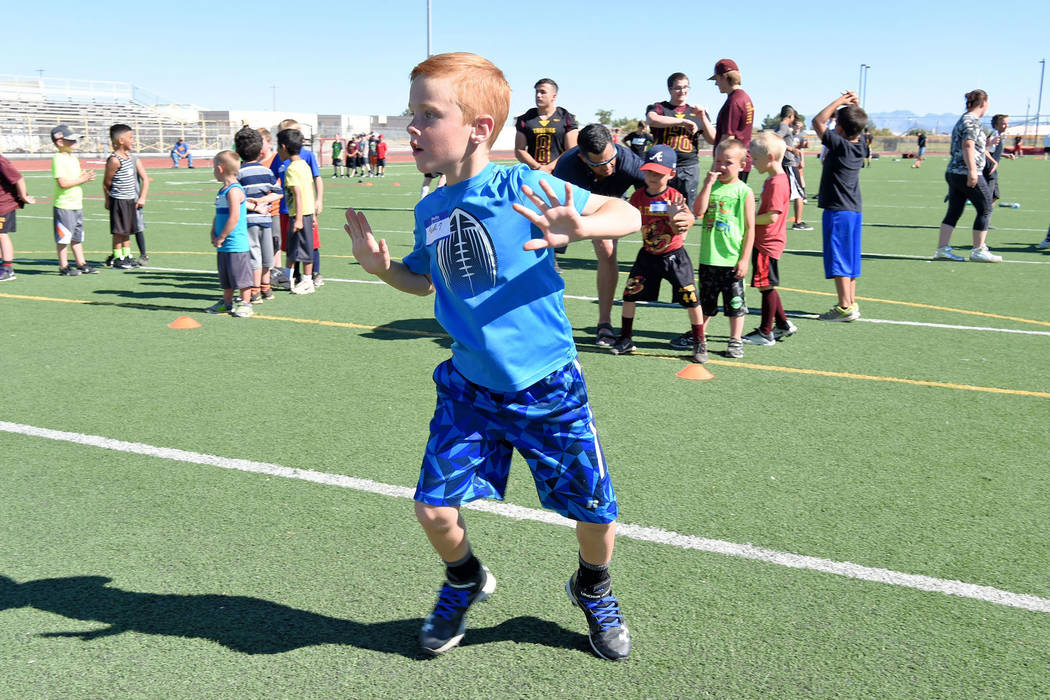 Peter Davis/Special to the Pahrump Valley Times Young Paul Walker, a youth football player, is showing off his technique.  The youth football camp had nearly 100 participants and was free of charg ...