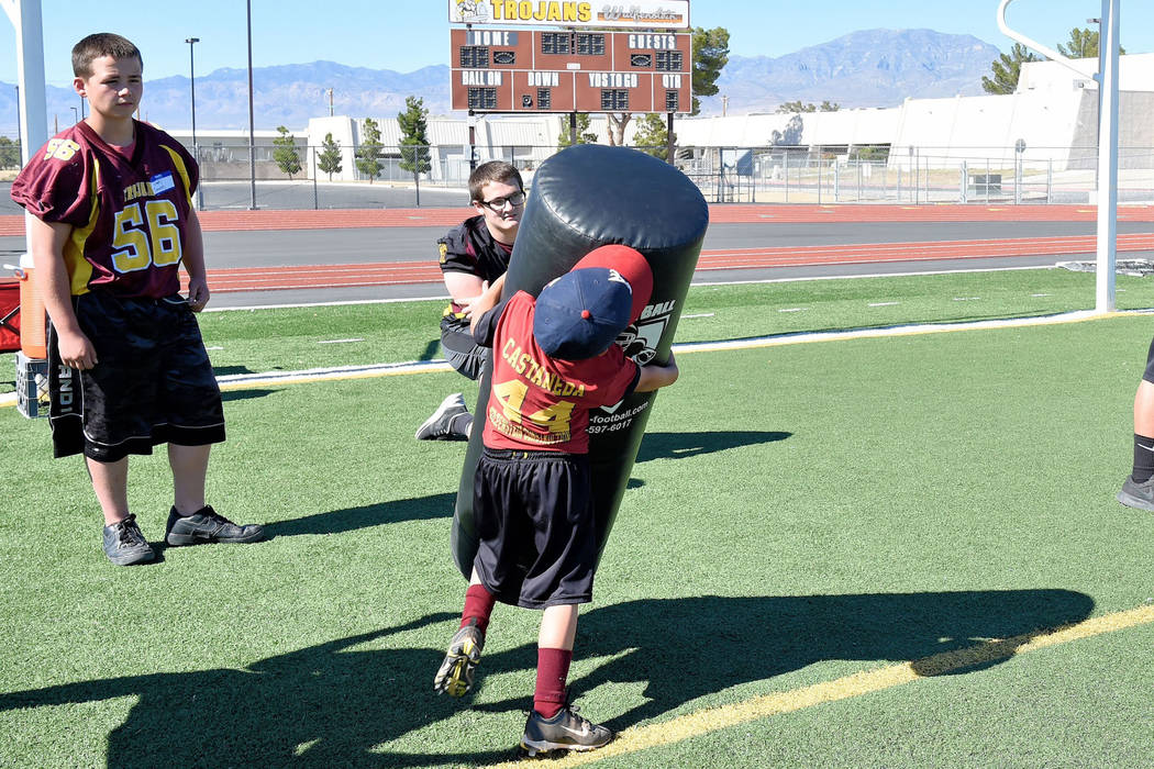 Photos by Peter Davis/Special to the Pahrump Valley Times  I got this: Cade Castaneda takes on a tackling dummy twice his size at the Junior Trojans Football camp at the high school over the weekend.