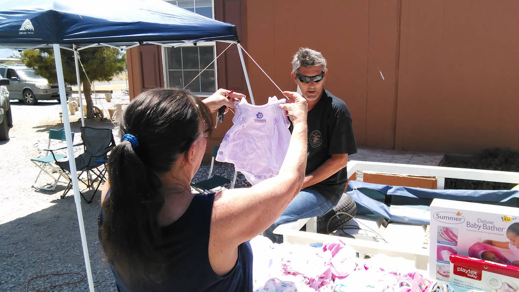 Selwyn Harris/Pahrump Valley Times A customer checks out baby clothing on May 27 during the chamber of commerce community yard sale as resident Mike Woods looks on. More than 50 homes in the commu ...