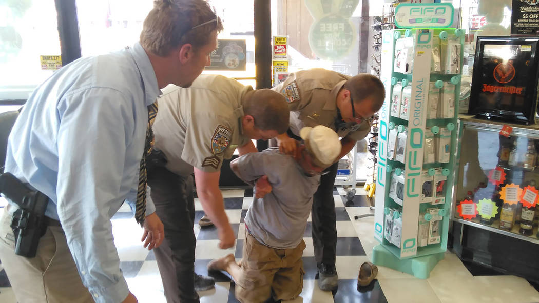 Selwyn Harris/Pahrump Valley Times  Nye County Sheriff's deputies and a detective apprehend Pahrump resident Richard Adams in the Rebel convenience store at Highway 160 and 372 on May 25. Adams  ...