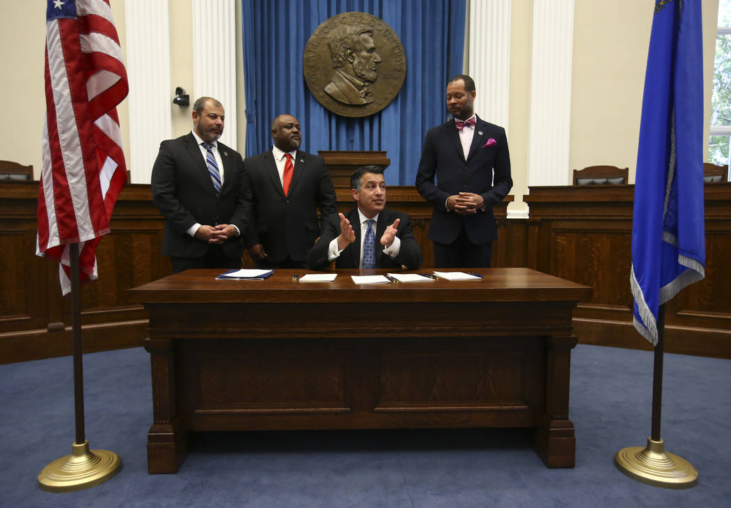 Chase Stevens/Las Vegas Review-Journal  Gov. Brian Sandoval, third from left, speaks before signing a group of bills while flanked by, from left, Assembly Minority Floor Leader Paul Anderson, R-La ...