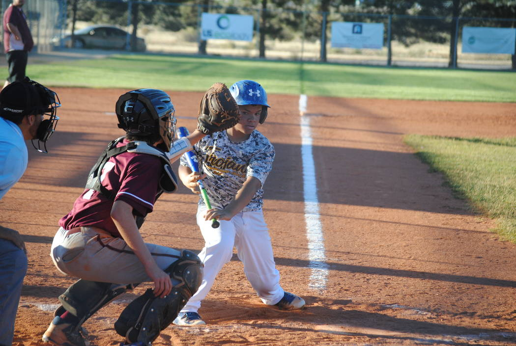Charlotte Uyeno/Pahrump Valley Times  Outfielder Brysten Marquez keeps an eye on the ball on May 20. The Trojans 14U team is off to a slow start, winning their first game against the Chargers Blac ...