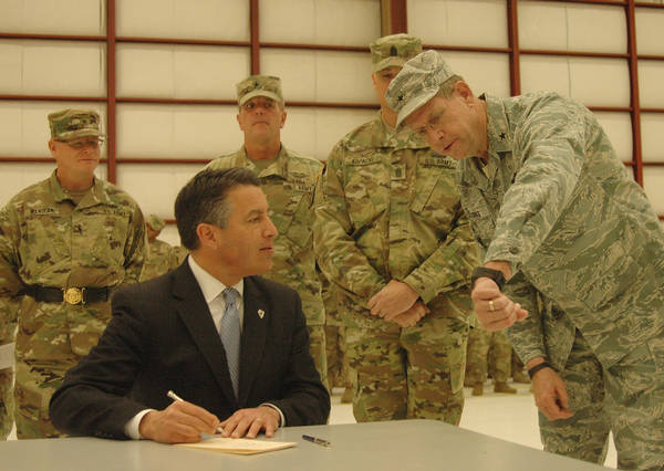 Erick Studenicka/Nevada National Guard Nevada Gov. Brian Sandoval asks Nevada Adjutant General Brig. Gen. Burks the exact time as he signs Assembly Bill 2 in Stead, Nev., on Sunday. Assembly Bill  ...