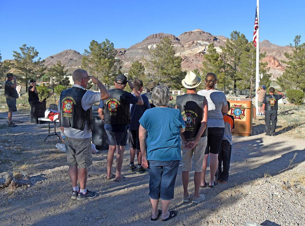 Richard Stephens/Special to the Pahrump Valley Times Crowd members salute while the national anthem is played and a flag that had been lowered to half-staff is raised back to the top of the pole J ...