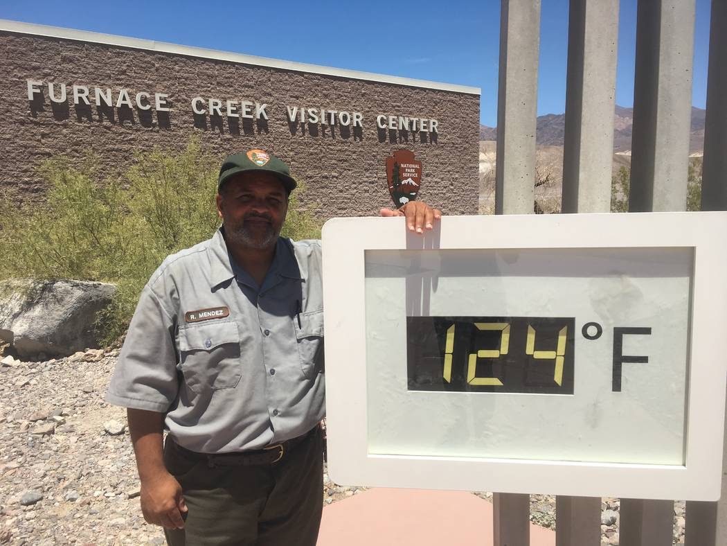 Special to the Pahrump Valley Times Death Valley National Park Ranger Roberto Mendez poses next to the thermometer at Furnace Creek Visitor Center on Sunday, June 18. The hottest place in the lowe ...