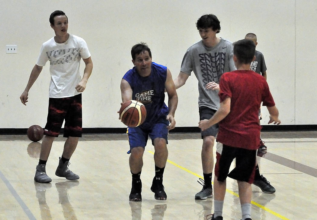 Horace Langford Jr./Pahrump Valley Times Coach Gil Llewellyn makes a move on Chance Farnsworth (in gray) during a scrimmage at the basketball camp. The camp took a hard look at basketball fundamen ...