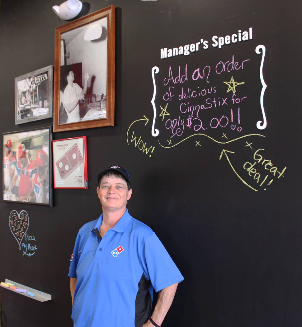 Jeffrey Meehan/ Pahrump Valley Times CJ Plunkett, general manager of Dominos Pizza in Pahrump, at 250 Highway 160, Ste. 6, stands for a photo in front of a chalk board where kids can get creative  ...
