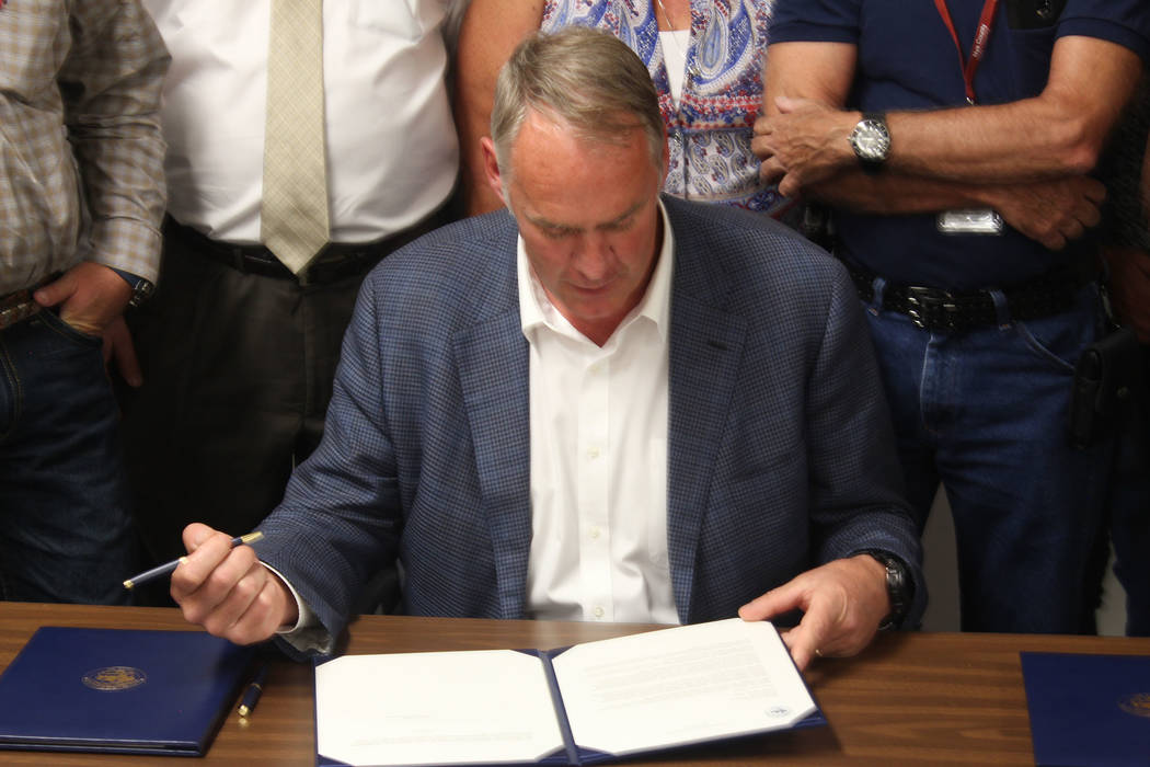 Jeffrey Meehan/Pahrump Valley Times Interior Secretary Zinke signs an order to release Payments in Lieu of Taxes funding for Nye County on June 26, 2017.