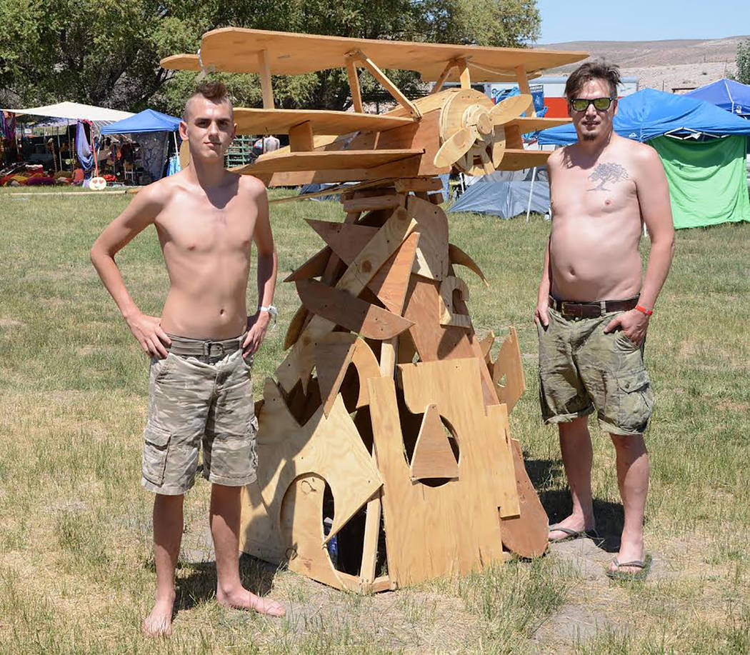 """Richard Stephens/Special to the Pahrump Valley Times Isaac and Michael Wright from the """"Post-Nuclear Family"""" camp with a sculpture of an airplane they made from scrap wood at the Southern Nevada R ..."""