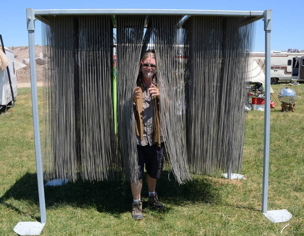 "Richard Stephens/Special to the Pahrump Valley Times An attendee walks through Anthony Bondi's ""Iron Curtain,"" a sculpture made up of more than a mile of strands of ball chain at the Southern Neva ..."