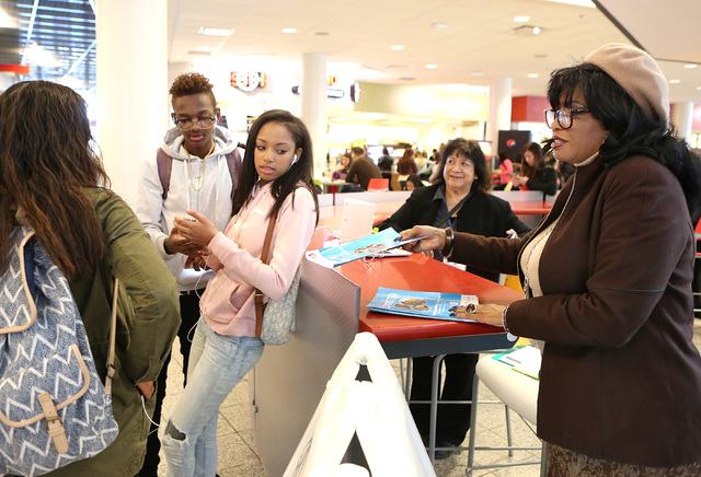 Bizuayehu Tesfaye/Las Vegas Review-Journal Cherie Hughes, right, a navigator with Nevada Health Link, hands out a brochure to UNLV students Cassie Middleton, left, Jaylen Allen, center, and Giahnn ...