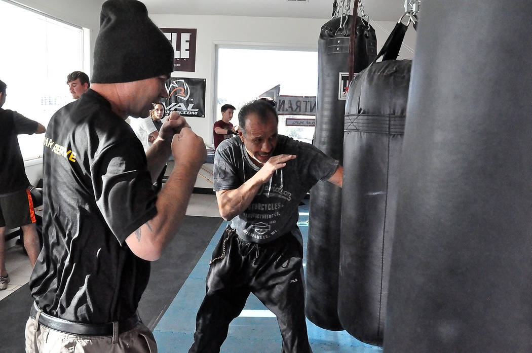 Horace Langford Jr./Pahrump Valley Times Boxing coach Ruben Bajo (on right), instructing class on hitting the bag. Bajo believes Mayweather should win the fight with his skill set.
