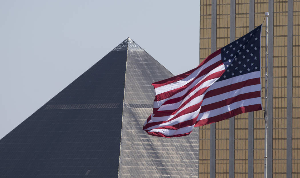 With the Luxor pyramid and Delano in the background, a large American flag blows in the wind above a Terrible Herbst gas station on West Russell Road and Polaris Avenue in Las Vegas on Sunday, Jul ...