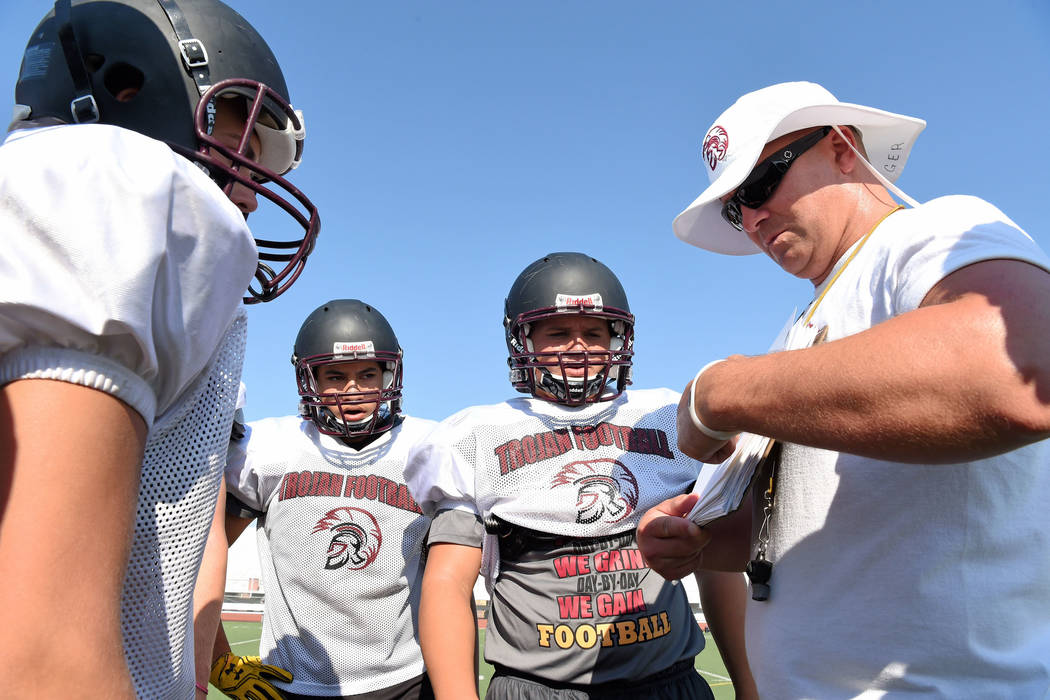 Peter Davis/Special to the Pahrump Valley Times Peter Davis/Special to the Pahrump Valley Times Trojans coach Craig Rieger goes over a play with the team. The Trojans start the season off hosting  ...