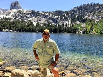 Gary Bennett Photography Gary Bennett stands in front of Lake George in Mammoth Lakes, California, with a waterfall in the background.