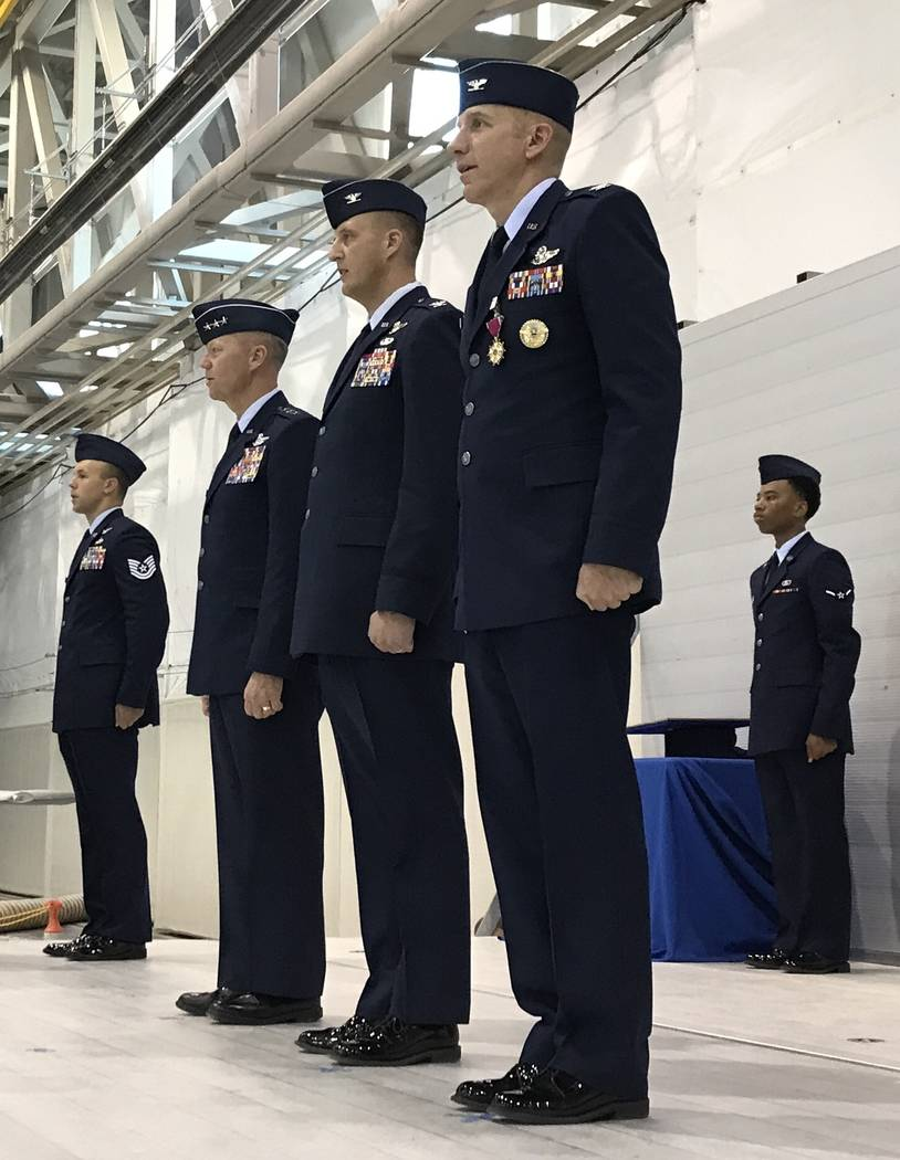 Air Force Lt. Gen. Mark Kelly, left, Col. Julian Cheater and Col. Case Cunningham stand at attention Thursday, July 6, 2017, with two enlisted airman inside the Reaper hangar at Creech Air Force B ...