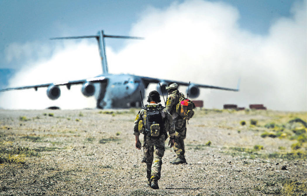 Las Vegas Review-Journal Ground controllers from the 23rd Special Tactical Squadron, from Hurlburt Field in Florida, walk toward a C-17 Gobemaster that landed on a desert strip at the Nevada Test  ...
