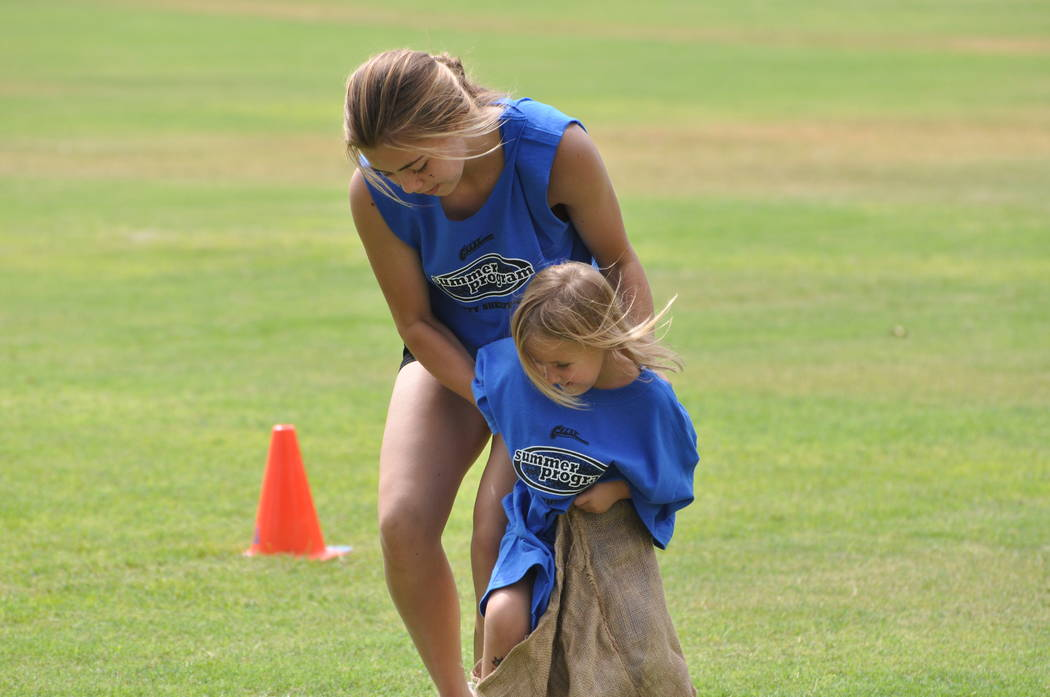 Photos by Horace Langford Jr./Pahrump Valley Times  Roadside assistance: Skyler Lauver lends a hand to a stuck sack racer, who got a flat tire during a sack race at the G.R.E.A.T Games last week a ...