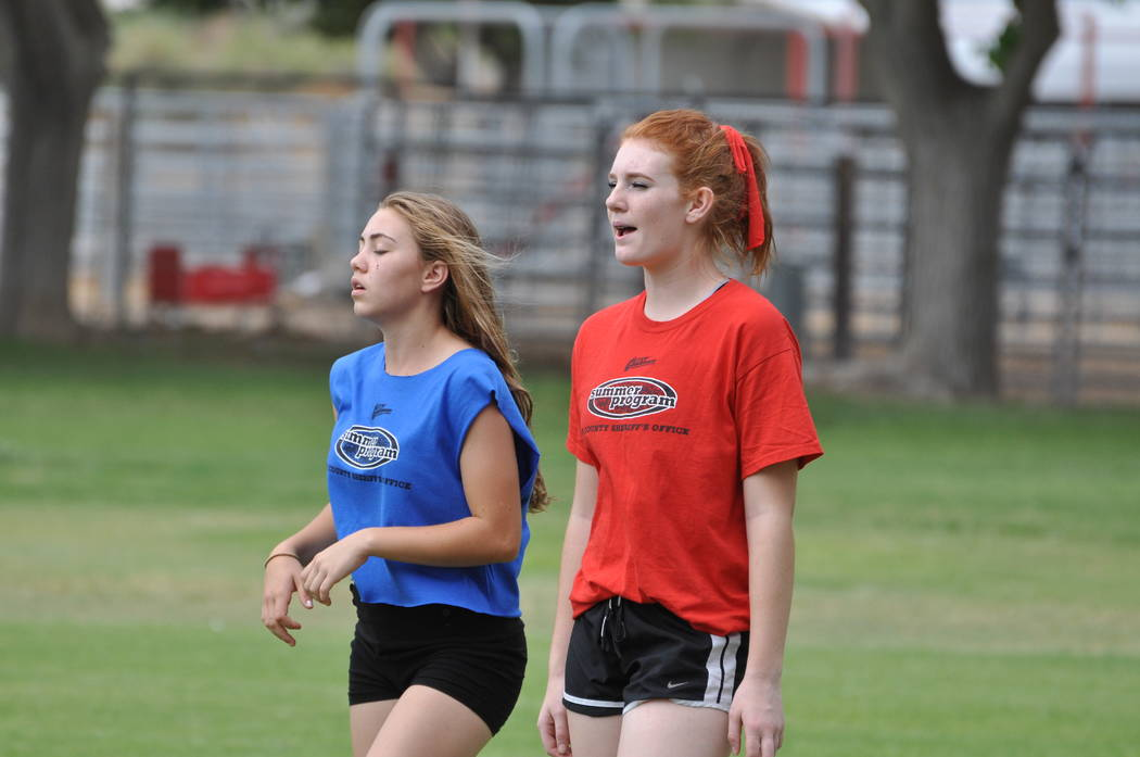 Melting volunteers: Two high school volunteers, Skyler Lauver, left, and Savannah Fairbank look like they need to be cooled down as temperatures soared to over 100 degrees for the games.