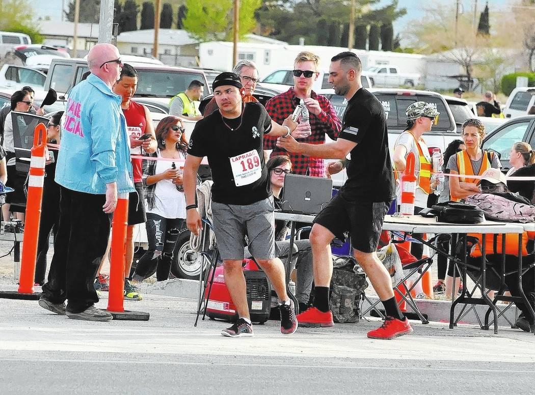 Horace Langford Jr / Pahrump Valley Times - Baker to Vegas Run, Saturday, Orange County Sheriff's Dept. runners passing the baton.