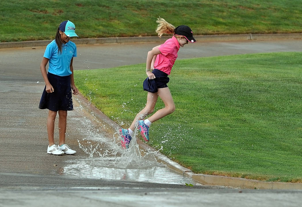 Golfers Ali Zuniga and Sasha Strain enjoy puddles after the storm while taking a break from the tournament on Wednesday because of rain showers on the course.