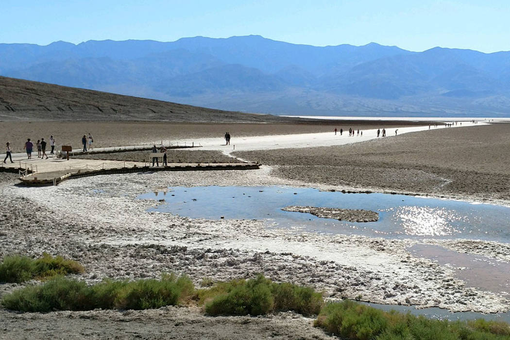 Tourists walk around Badwater in Death Valley National Park in California in summer 2017. Badwater, at 282 feet below sea level, is the lowest point in the Western Hemisphere. It is often the hott ...
