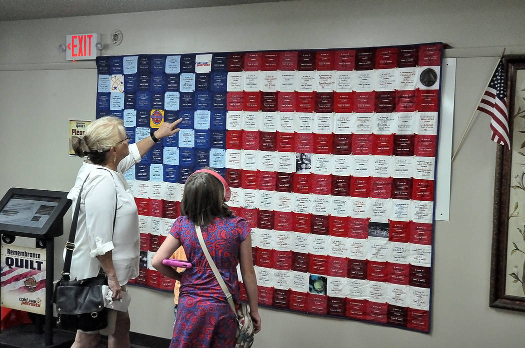 Horace Langford Jr./Pahrump Valley Times -   Janet Hansen, of Pahrump, and her grandchildren, look at the quilt commemorating former nuclear weapons and uranium workers. The quilt is the centerpie ...