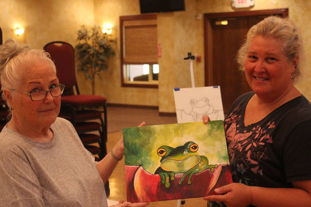 Jeffrey Meehan/Pahrump Valley Times Doris Smith, student (left), and Laurie McCaslin instructor (right), hold a Prince Charming painting on Aug. 12, 2017. McCaslin instructs a three-hour course ev ...
