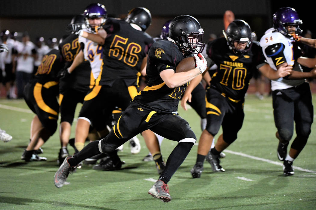 Peter Davis/Special to the Pahrump Valley Times David Roundy heads for open field in the second half as the Trojans played catch-up with their running game. Pahrump Valley took seven minutes off t ...
