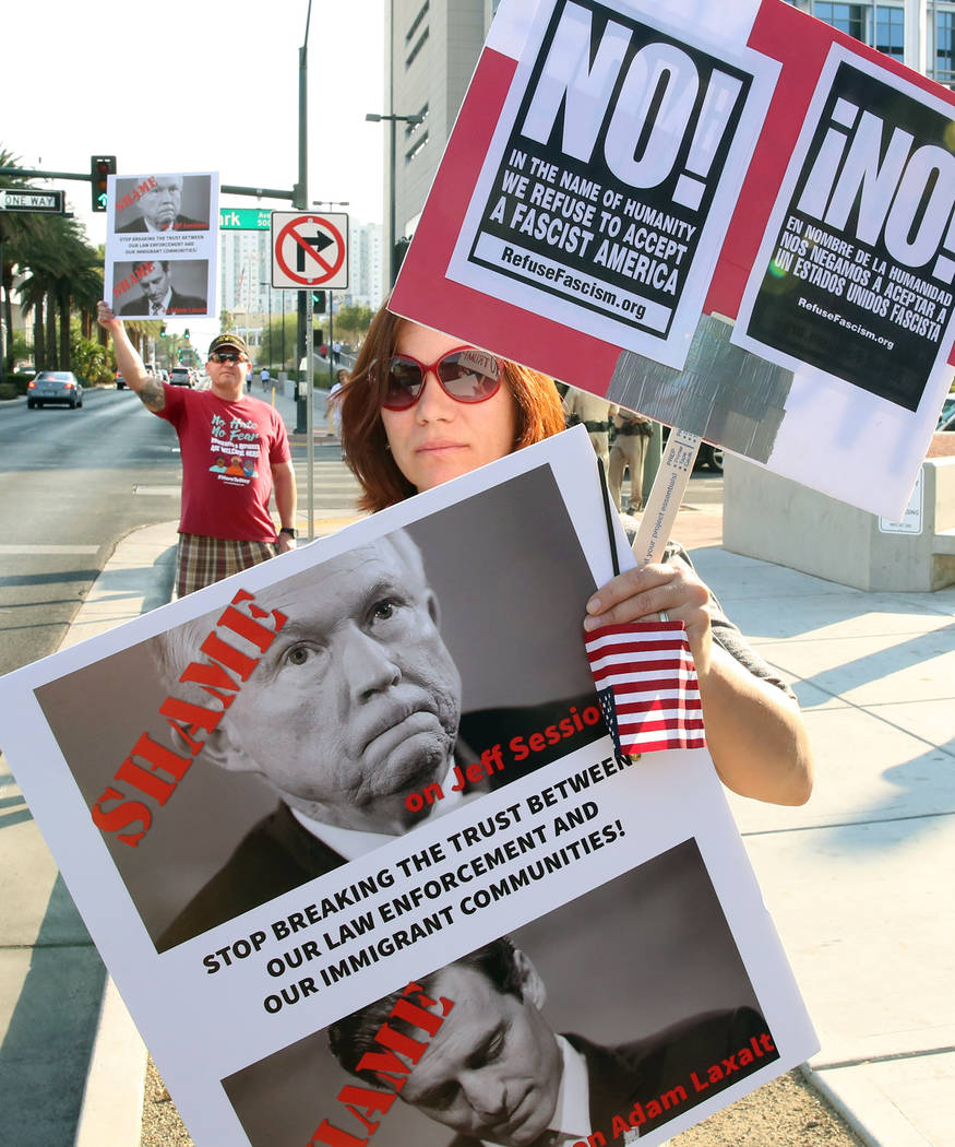 Bizuayehu Tesfaye/Las Vegas Review-Journal  A protester, who declined to give her name, protests against sanctuary cities ban outside a federal building where Attorney General Jeff Sessions delive ...