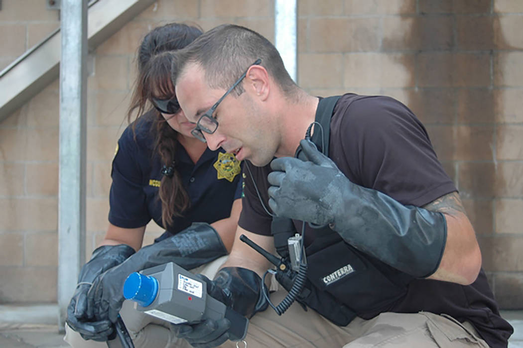Erick Studenicka/Nevada National Guard  Sgt. Bill Frederick of the 92nd Civil Support Team searches for potential radiological material at a mock dirty bomb laboratory with University Police Offic ...
