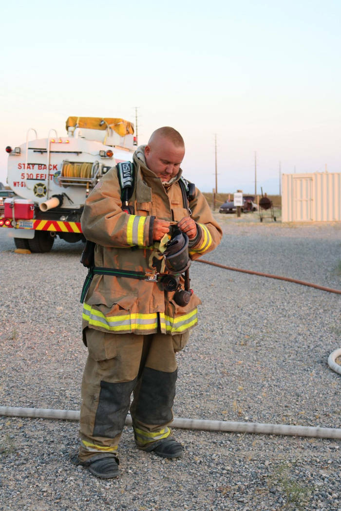 Special to the Pahrump Valley Times Nye County Technical Response Station 51 firefighter Thomas Kloiber makes adjustments to his breathing apparatus just prior to departing Station 51 on Thursday, ...