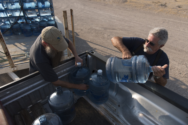 Southern Inyo Fire Protection District chief Larry Levy, right, and Jim Furlough make their weekly potable water delivery rounds to residents in Tecopa, Calif., on June 21, 2016. The delivery serv ...