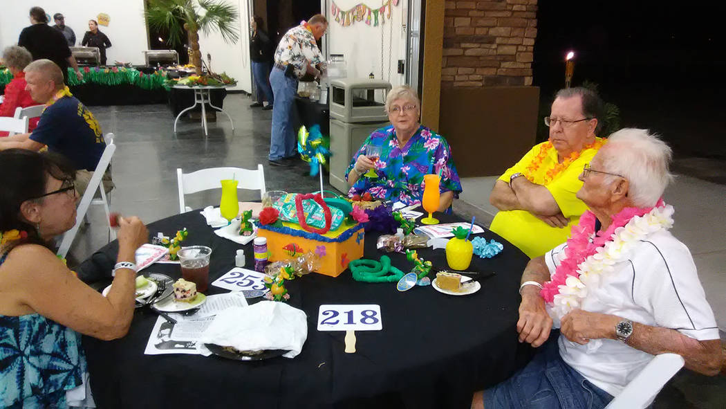 Selwyn Harris/Pahrump Valley Times Casa Luau attendees lounge outdoors prior to the beginning of the auction portion of the program. The spotty weather eventually gave way to sunshine during the e ...