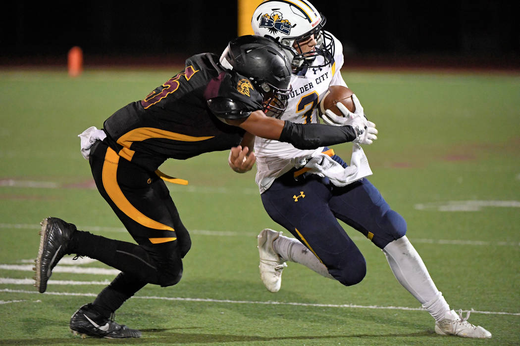 Senior Trojans safety Jacob Sawin sacks Boulder City's quarterback for a loss as he tries to escape the Trojans defense. The Trojans are now 2-2 in preseason and open league play on Sept. 28 aga ...