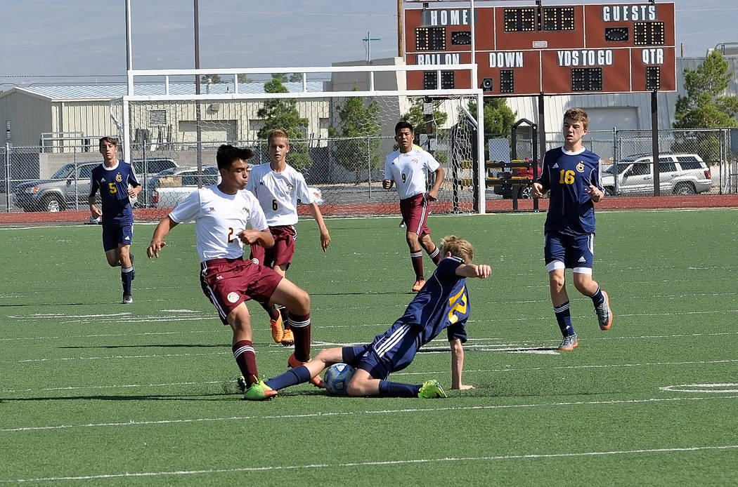 Trojans freshman midfielder Jalen Denton fights for the ball with a Boulder City player. Pahrump Valley dominated the first half only to let the game slip away in the second.